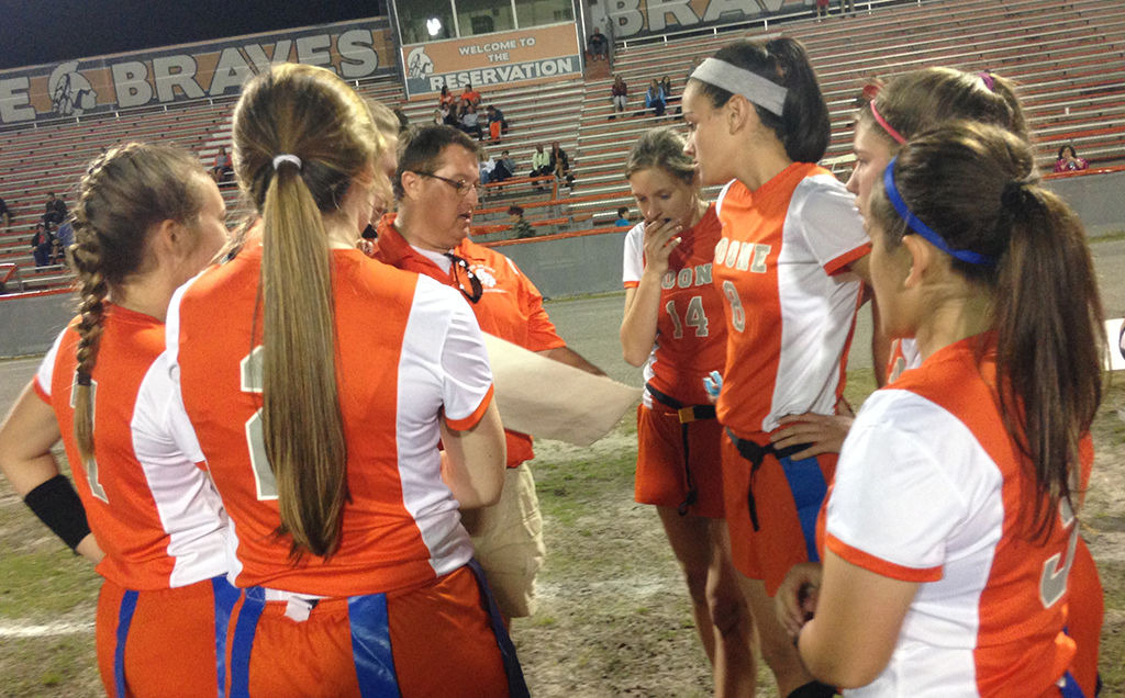LISTEN UP. At halftime coach Ken Hensley discusses plays with the team. photo/Maddy Bogan