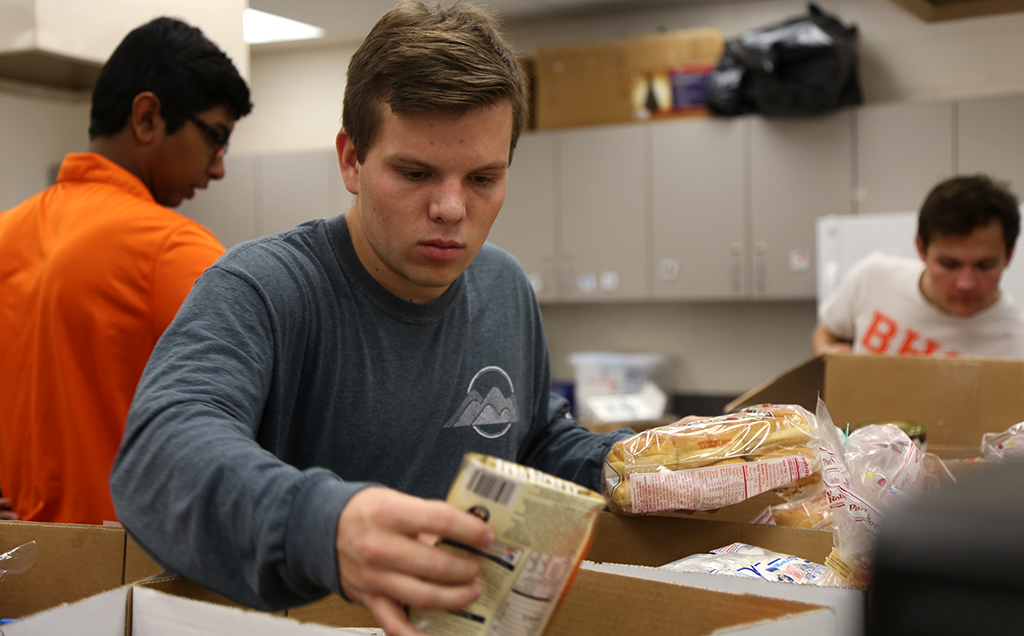 PACK IT UP. Senior David Emsley packs one of the Thanksgiving Baskets. Photo/Douglas Page