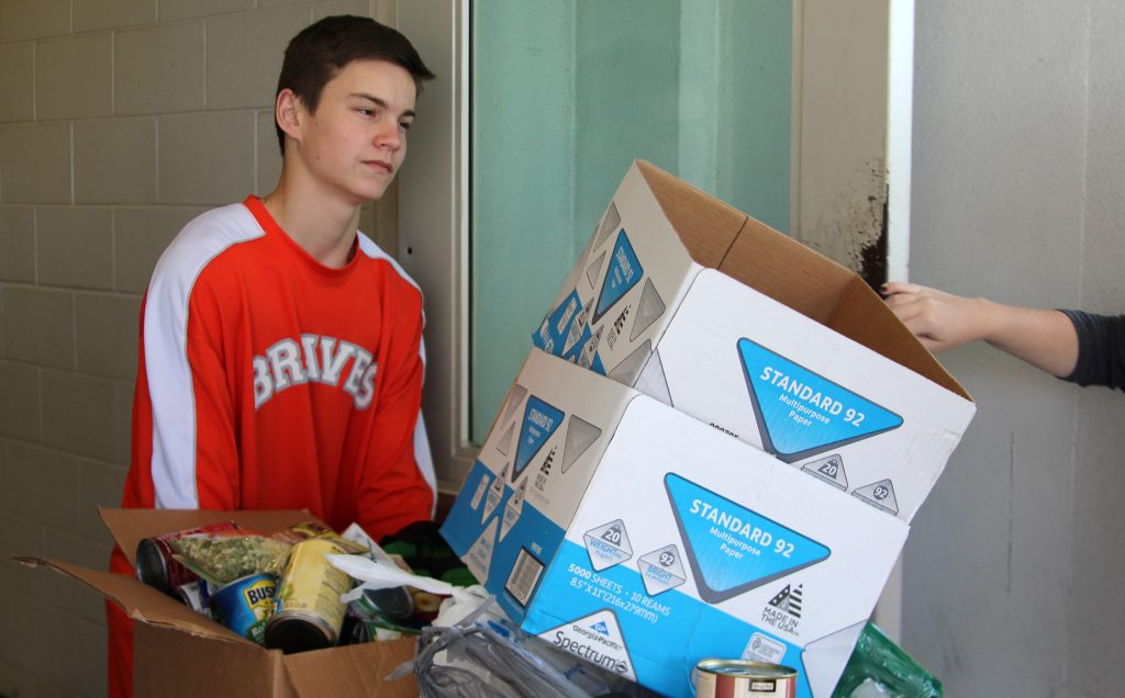 LOAD IT UP. Freshman Sean McCabe transports the food back to Mrs. Hines room. photo/Emily Fussell