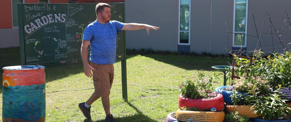 Josh points to plants in butterfly garden