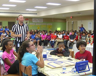 Referee and students read a question in Science competition